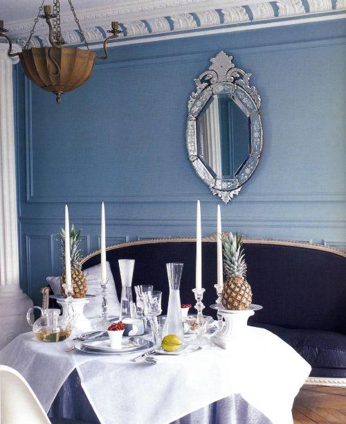 Стена в этой столовой окрашена в бледно-голубой цвет, на фоне которой акцентируют венецианское зеркало XIX в. и старинный диван.