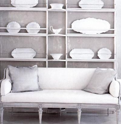 Комбинация белых и серых тонов в скандинавском стиле. Изначальную симметрию создают китайский фарфор, расставленный на полках, и диван.