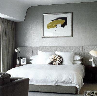 В спальне дорогого отеля стены, кровать, диван и занавески решены в изысканных сероватых оттенках.