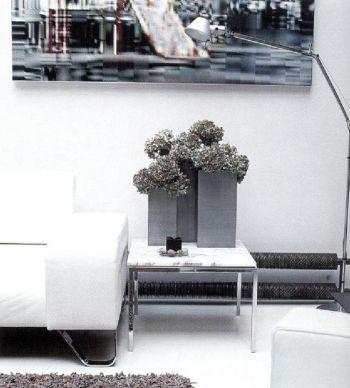 Для того чтобы ввести в жилое помещение еще один оттенок серого, дизайнер Кристиан Торту использует три цинковые вазы.