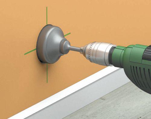 Резка отверстия под розетку — при помощи коронки по бетону в стене прорезается отверстие, сверло приставляется к центру пересечения линий