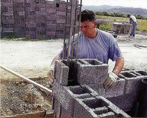 2. Возведение стены начинаем с угла. Устанавливаем специальный угловой блок, выравниваем его с двух сторон и усиливаем арматурой.