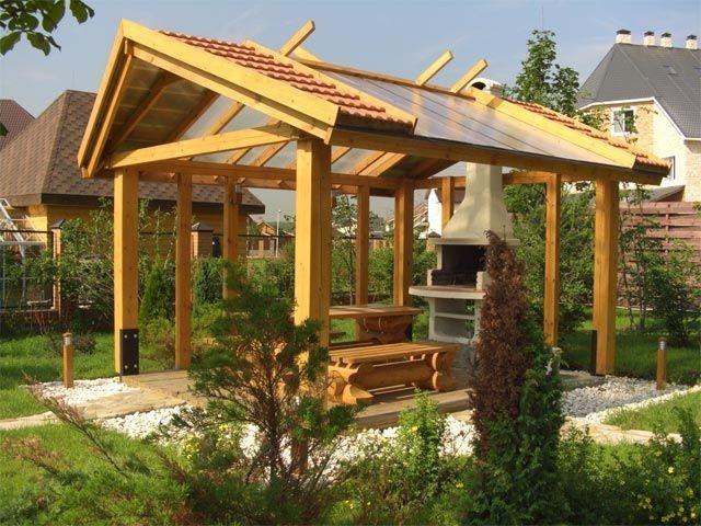 Открытая беседка, расположенная возле дома, оборудована печью-барбекю и оригинальной прозрачной крышей.