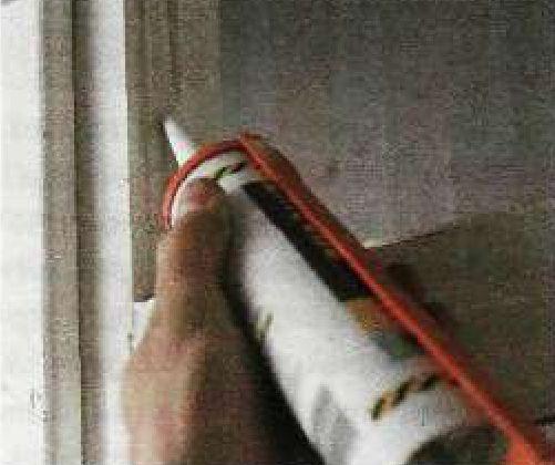 Закладка уплотняющей массы в щели окна.