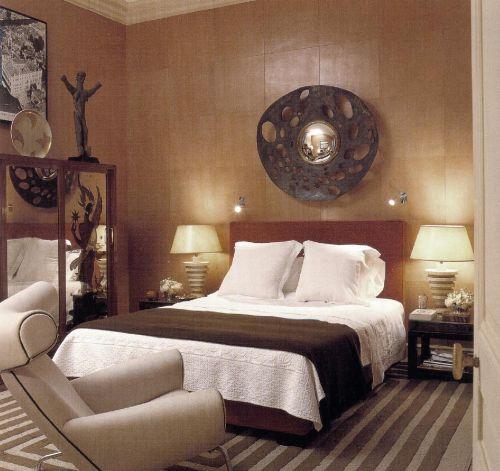 Дизайнер Альберто Пинто в качестве напольного покрытия выбрал ковер современного рисунка, цвет которого превосходно сочетается с имбирным цветом стен; кровати и покрывала темного кофейного оттенка. Зеркало изготовлено в мастерской Эрве ван дер Штретена.