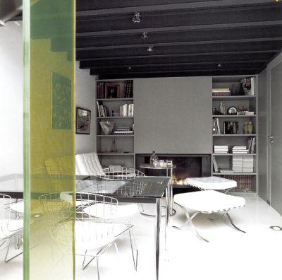 Через прозрачную панель ярко зеленого цвета мы смотрим на обеденное пространство, которое обставлено мебелью из металла, стекла и белой кожи. Панель состоит из цветного пластика и двух прозрачных стекол.
