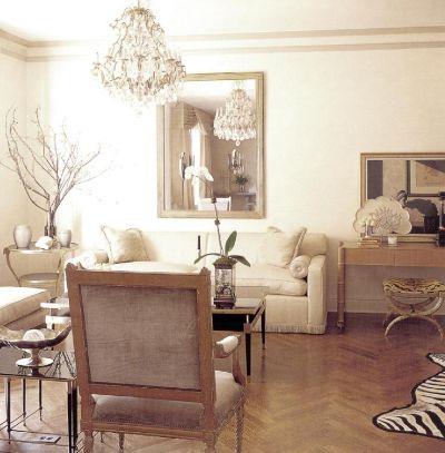Солнечная светлая атмосфера гостиной с паркетом золотистого тона еще более усилена позолотой, зеркалами и стеклом. Принт с рисунком звериной шкуры придает комнате черты современного стиля.