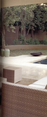 Жилое пространство создано по проекту дизайнера Фальке. Садовая зелень на заднем плане прекрасно вписывается в интерьер этой открытой комнаты. Коллекция южноафриканских сосудов вносит в ее атмосферу колорит экзотики.