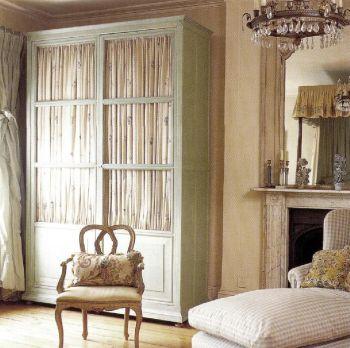 Платяной шкаф с прозрачными проволочными дверцами, позади которых можно повесить собранную в складки ткань, придает уют этой спальне. Ткань в бледную клетку на подушках создает лавандовый акцент.