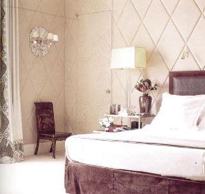 В атмосферу этого интерьера дизайнер Альберто Пито внес добавление в виде тисненых стенных панелей из шерсти. Ковер цвета капучино хорошо оттеняется каркасом кровати и стула.