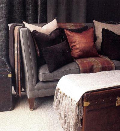 На диван оттенка темного инжира Берни дела Куона положила декоративные подушки из льняной ткани овсяного оттенка, из шоколадной замши и из ярко-оранжевой ткани.