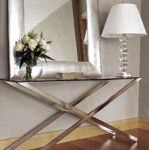 Серебряное зеркало на фоне серой стены хорошо сочетается со стеклянной лампой и стальным столом.