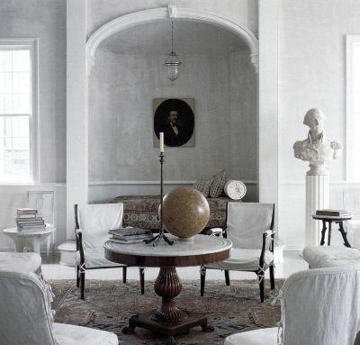 Серые стены этого интерьера, оформленного по проекту Фрэнка Фолкнера, - голая оштукатуренная поверхность. Стулья накрыты белыми чехлами.