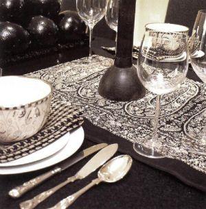 Дизайнер Берни де ла Куона часто меняет облик, своей столовой, используя различные ткани, например эту черную вышитую льняную дорожку.