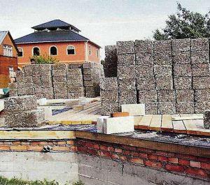 При строительстве дома из арболита цоколь делают из кирпича или бетона, подняв его выше отмостки на 50 см.