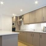 Создание зон освещения при помощи встроенных в гипсокартонный потолок светильников с галогенными лампами: видны зоны освещения кухонных шкафов и стойки