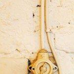 Устаревший способ наружной прокладки: кабель прикреплен к стене электроустановочной скобой и ничем не защищен