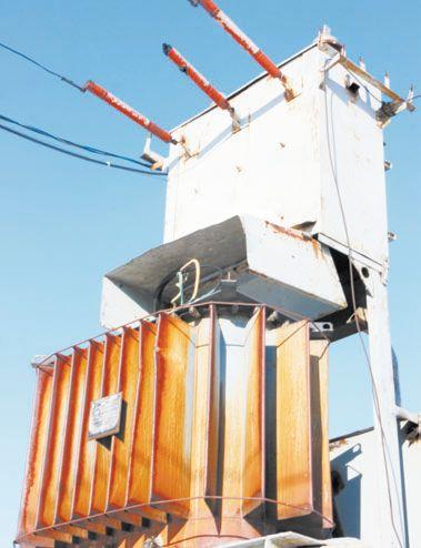 Трансформатор на подстанции понижает напряжение от высоковольтной линии для передачи в бытовую сеть