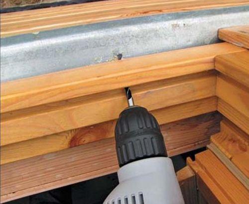 С помощью шуруповерта с битой-сверлом прочищаем отверстия для отвода влаги