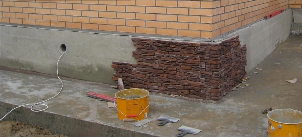 Облицовка цоколя дома панелями искусственным камнем