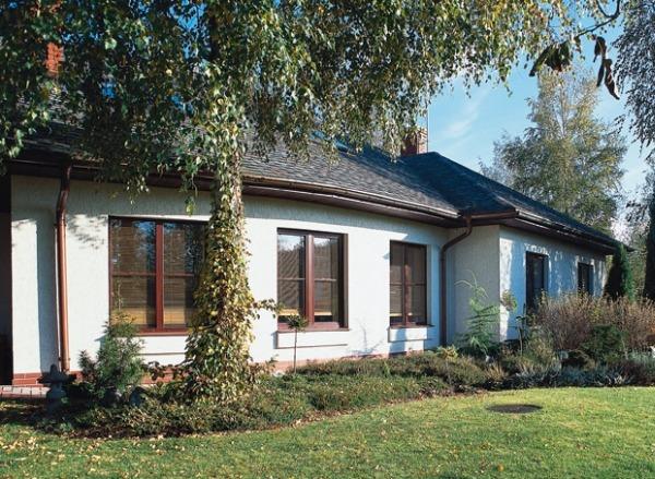 Одноэтажный, развитый по горизонтали дом состоит из двух прямоугольных блоков, стоящих под углом.