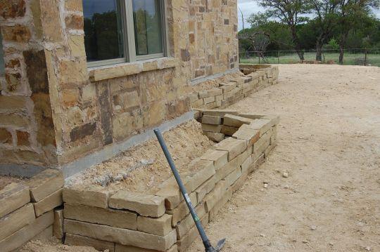 Вариант клумбы со стенками из камня, сделанной по периметру всего дома
