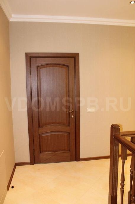 Шпонированная дверь установленная в загородном доме